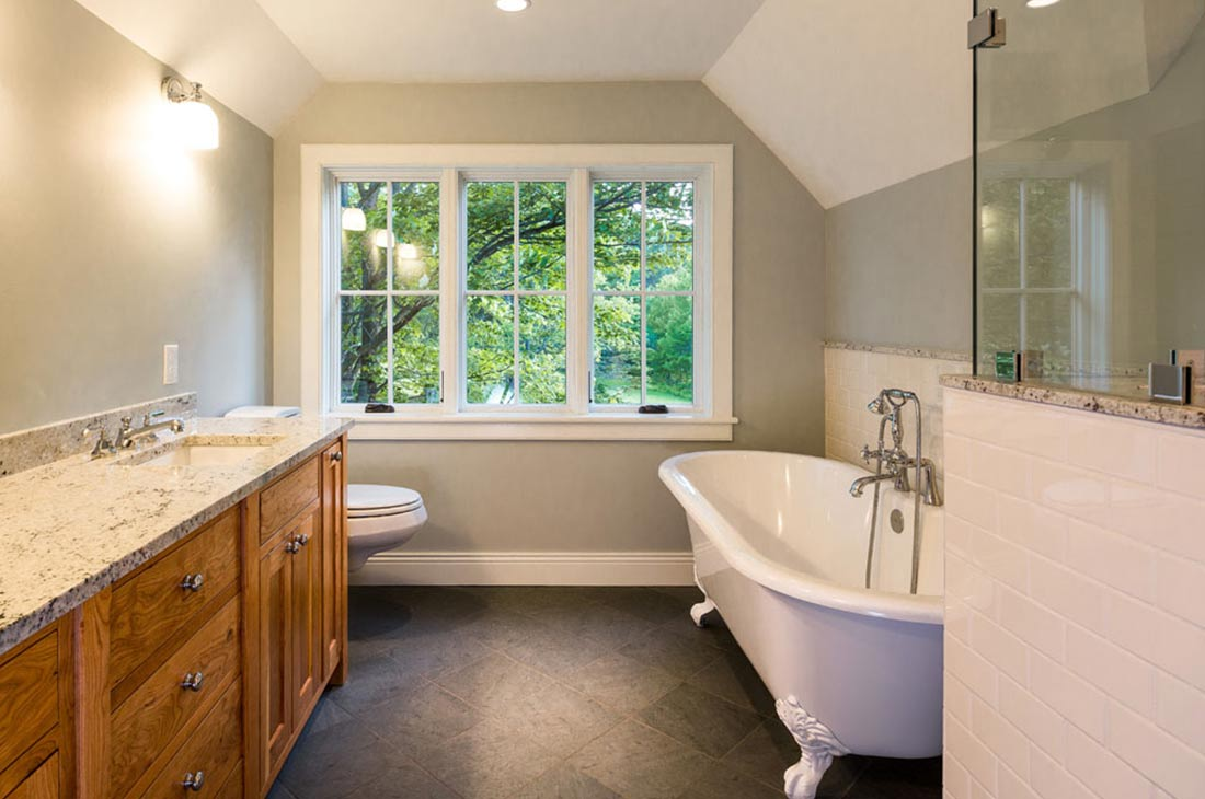 bathroom with clawfit tub and large window