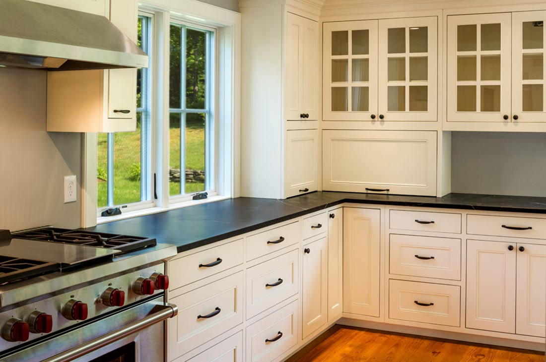white kitchen with dark countertop and gas range