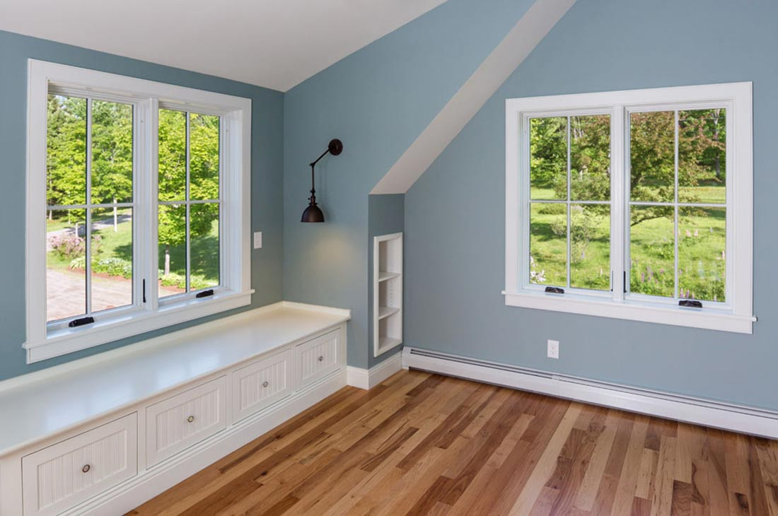 blue bedroom with built in shelves and bench seat